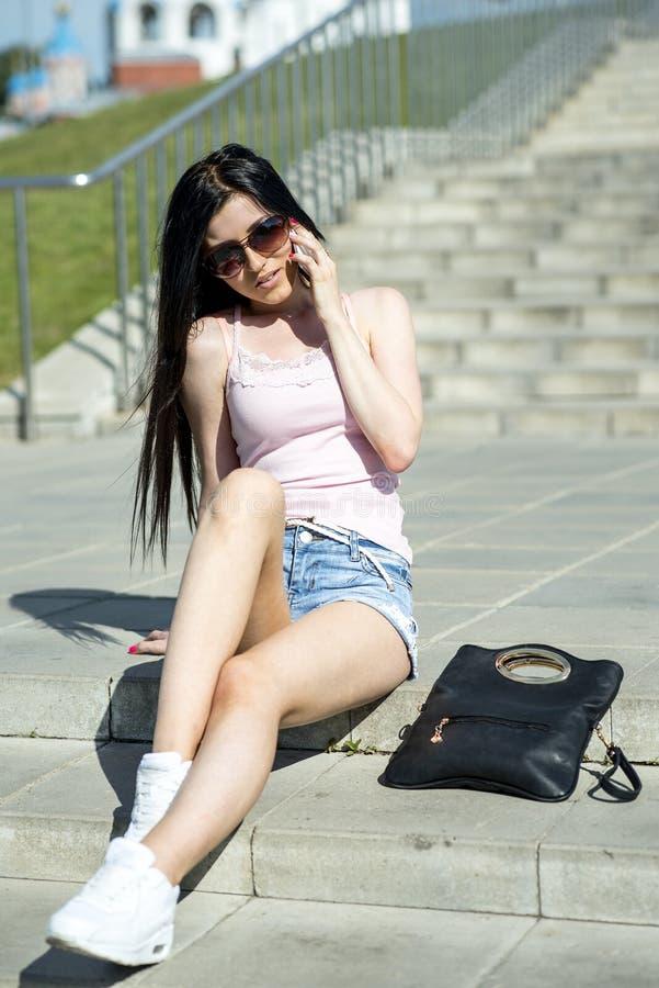 Schönes sexy Modemädchen, das auf Treppe sitzt und die liegende folgende Tasche des Telefons spricht lizenzfreie stockfotografie
