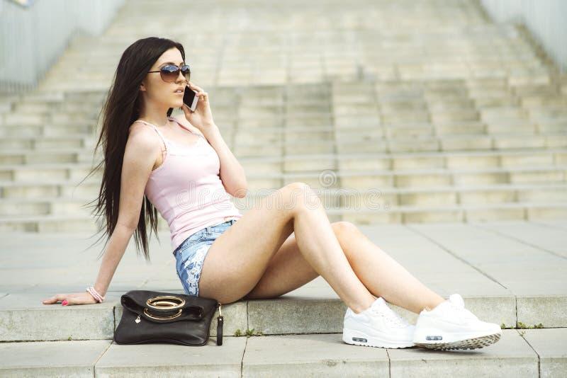 Schönes sexy Modemädchen, das auf Treppe sitzt und die liegende folgende Tasche des Telefons spricht stockfoto