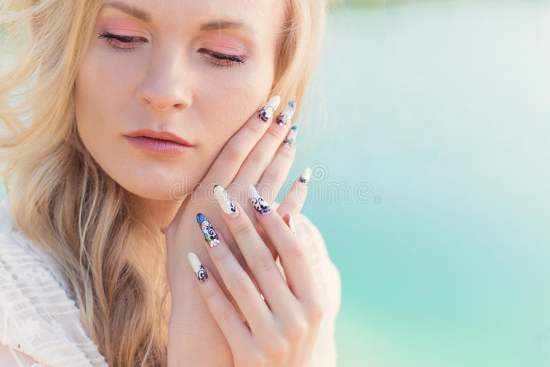 Schönes sexy nettes leichtes blondes Mädchen im weißen Kleiderhändchenhalten nahe dem Gesicht mit langen Acrylnägeln stockbilder