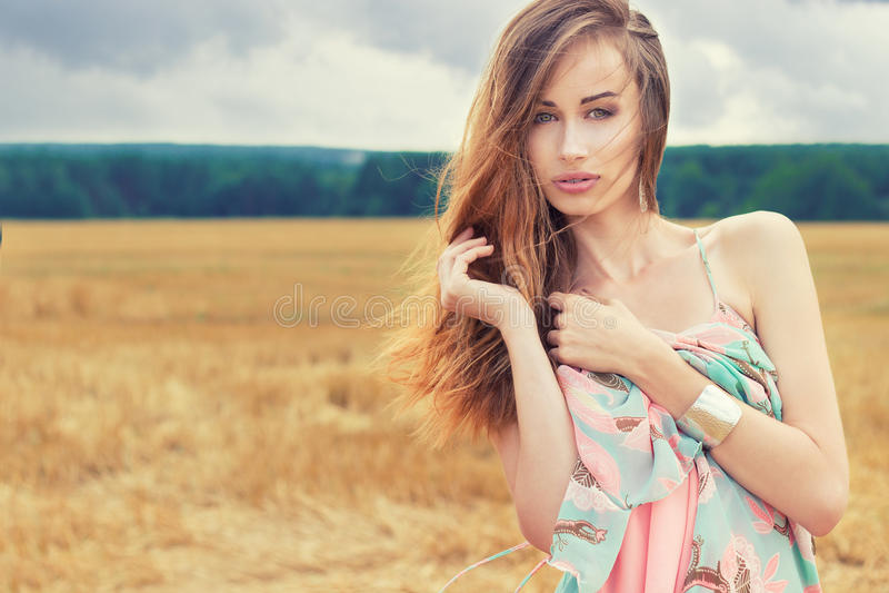 Schönes sexy romantisches Mädchen mit dem roten Haar, das ein farbiges Kleid, den Wind steht auf dem Gebiet an einem bewölkten So stockfoto