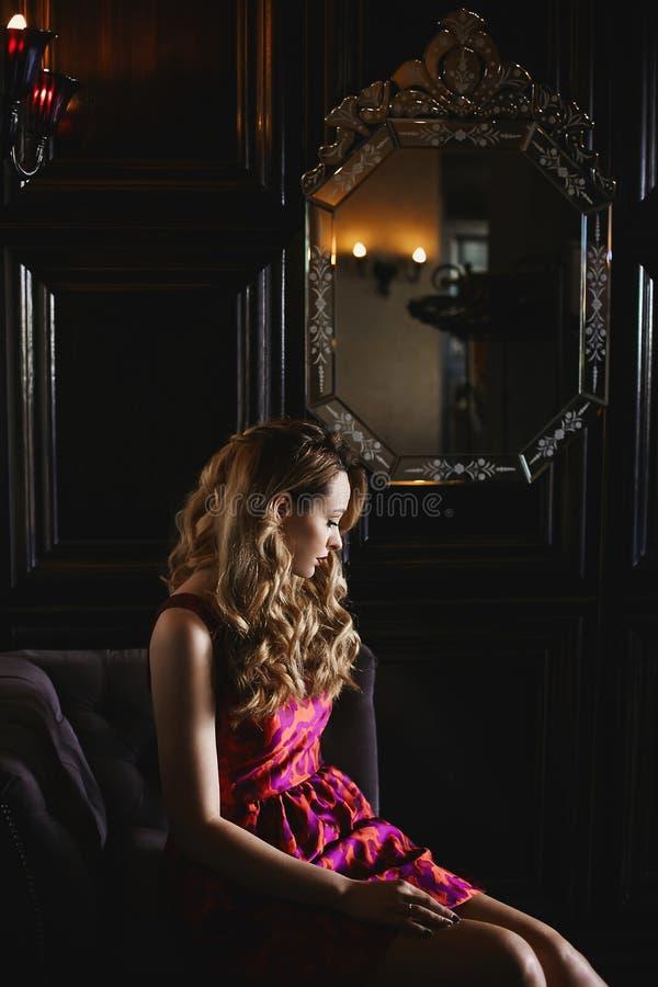 Schönes, sexy und modernes blondes Mädchen in einem roten Kleid wirft im dunklen Luxusinnenraum auf stockbild