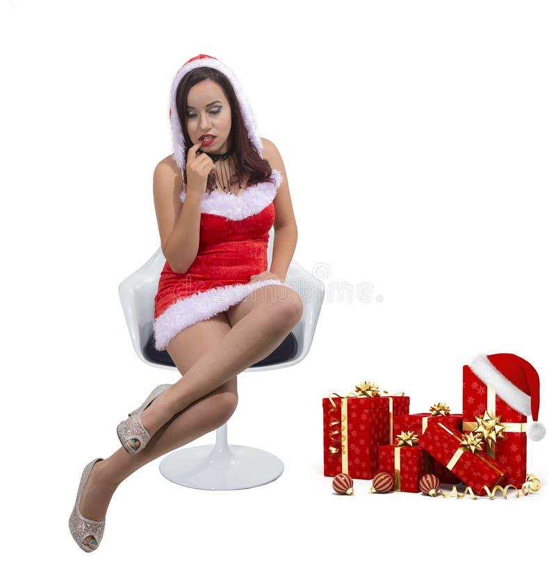 Schönes sexy Weihnachtsmädchen, das Santa Claus-Kostümeinstellung auf Stuhl neben Geschenken trägt stockfotos