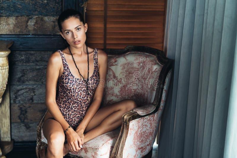 Schönes sinnliches Modell im Leopardbadeanzug sitzt auf Stuhl im Raum lizenzfreie stockfotografie