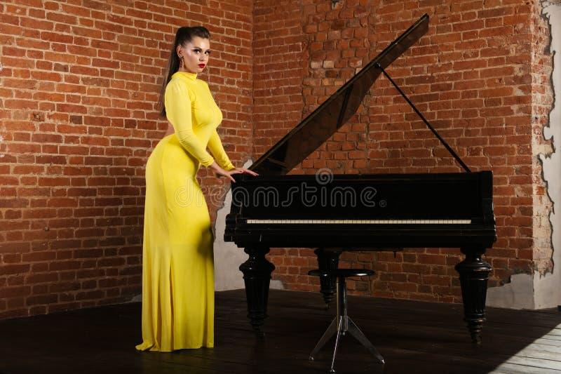 Schönes sinnliches und sexy blondes Mädchen in einer gelben Kleiderstellung nahe dem Klavier stockfoto