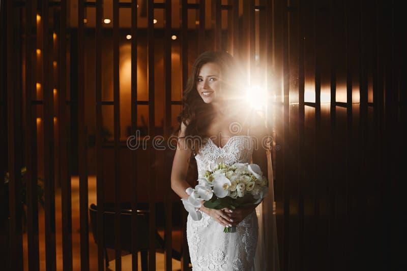 Schönes, sinnliches und sexy Brunettemodellmädchen mit hellem Make-up im modernen weißen Spitzekleid mit Blumenstrauß von Blumen  lizenzfreie stockfotografie