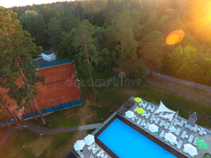 Schönes Sommerpool der Vogelperspektive mit den sunbed und Tennisplatzsonnenschirmen und in einer LandErholungsstätte Konzept von stockfotografie