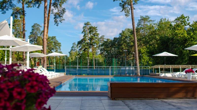 Schönes Sommerpool mit sunbed und Sonnenschirme in einer LandErholungsstätte Konzept der Erholung und der Freizeit lizenzfreie stockbilder