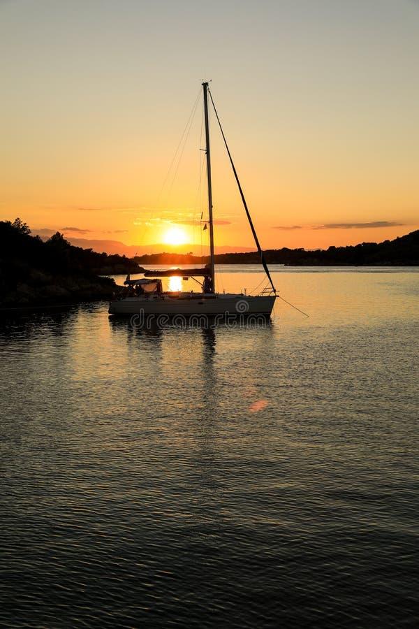 Schönes Sonnenuntergangsegelboot, das in einer Bucht nahe Porto Heli, Peloponnes, Griechenland verankert stockfotos