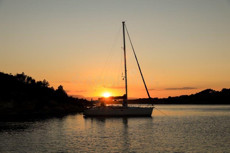 Schönes Sonnenuntergangsegelboot, das in einer Bucht nahe Porto Heli, Peloponnes, Griechenland verankert lizenzfreies stockfoto