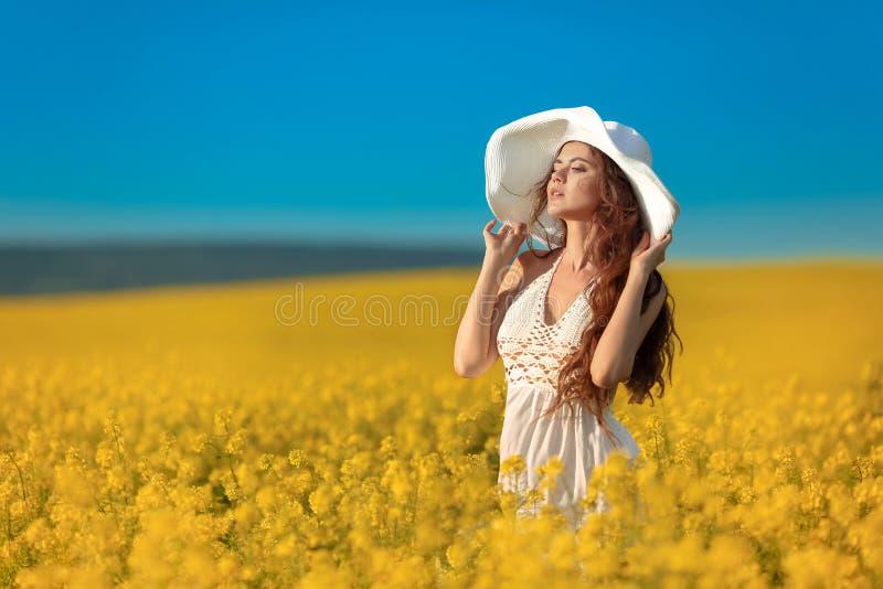 Schönes sorgloses Mädchen im weißen Hut über gelbem Rapsfeldlandschaftshintergrund Attracive-Brunette mit dem langen gelockten ge stockfotos