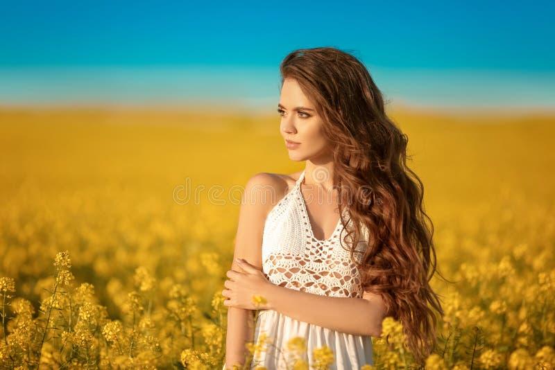 Schönes sorgloses Mädchen mit dem langen gelockten gesunden Haar über gelbem Rapsfeldlandschaftshintergrund Attracive-Brunette mi lizenzfreie stockfotos