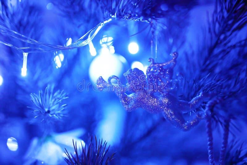 Schönes Spielzeug in Form eines Engels mit den Flügeln, die eine Trompete hängt an einem Weihnachtsbaum angesichts der blauen Gir stockfotografie