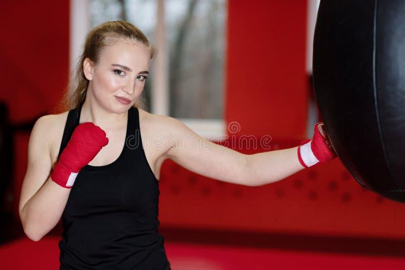 Schönes sportliches Frauenverpacken mit rotem Sandsack an der Turnhalle lizenzfreie stockfotos