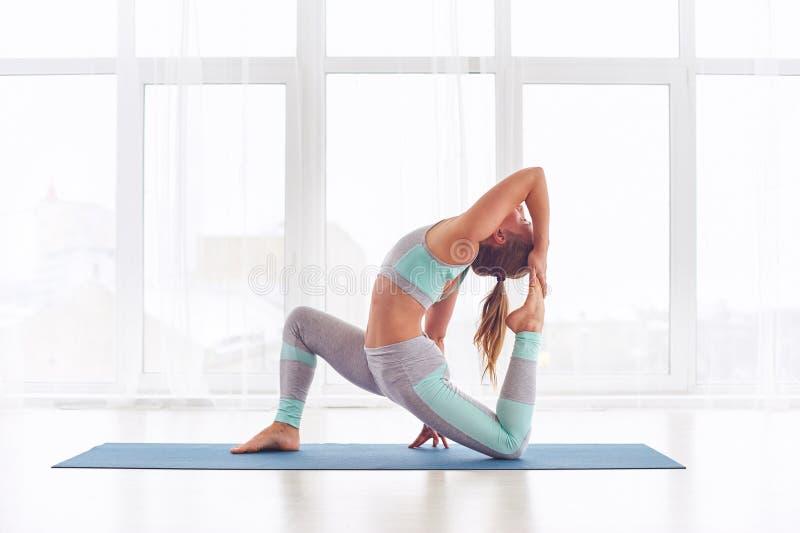 Schönes sportliches rajakapotasana Haltung Sitzjogifrauenpraxisyoga asana Königs Pigeon am Yogastudio lizenzfreie stockfotografie