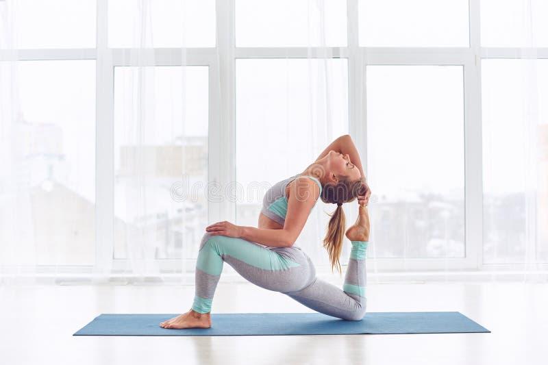 Schönes sportliches rajakapotasana Haltung Sitzjogifrauenpraxisyoga asana Königs Pigeon am Yogastudio stockfotos