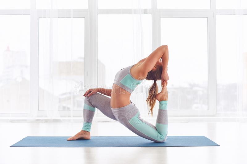Schönes sportliches rajakapotasana Haltung Sitzjogifrauenpraxisyoga asana Königs Pigeon am Yogastudio stockfotografie
