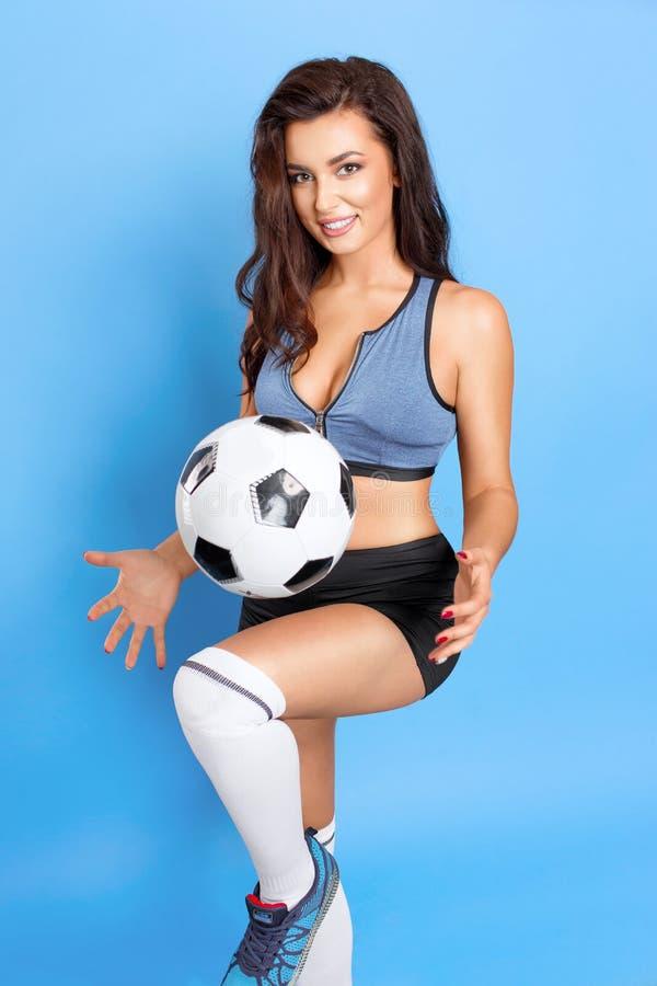 Schönes Sportmädchen, das mit einem Ball als Fußballspieler auf einem blauen Hintergrund aufwirft stockfotografie