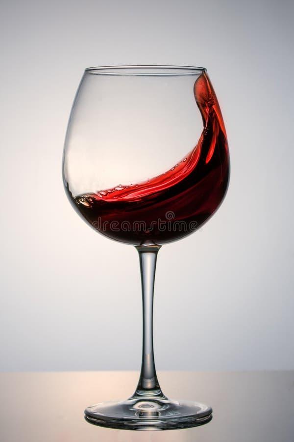 Schönes Spritzen des Rotweins in einem Glas lizenzfreies stockfoto