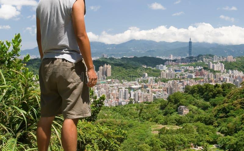Schönes Stadtbild mit einem Mannstandplatz und -uhr weit lizenzfreie stockbilder