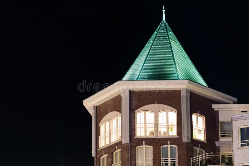 Schönes Stadtturmgebäude mit beleuchteten Wohnungsfenstern und eine spitze Dachspitze, moderne niederländische Architektur nachts lizenzfreies stockfoto