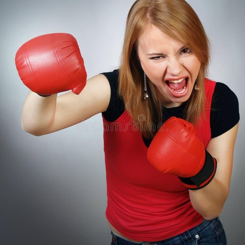 Schönes starkes Mädchen in den roten Handschuhen für Verpacken lizenzfreie stockfotos
