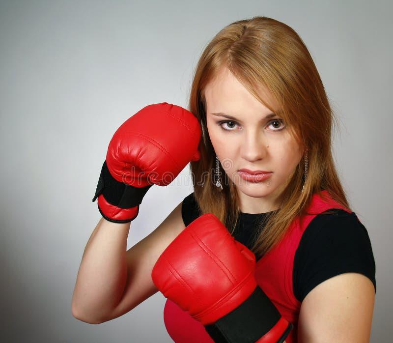 Schönes starkes Mädchen in den roten Handschuhen für Verpacken lizenzfreies stockfoto