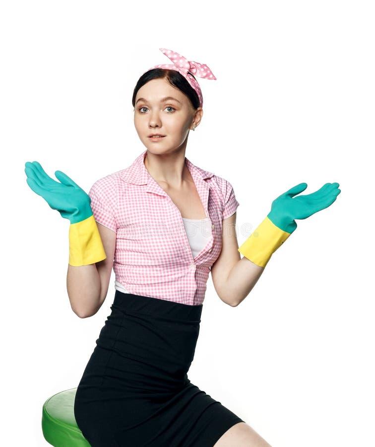 Schönes Stift-up-Mädchen in einem rosa Hemd mit Gummihandschuhen zum Reinigen des Lächelgrauen, Armen zur Seite, Handflächen nach stockfotos