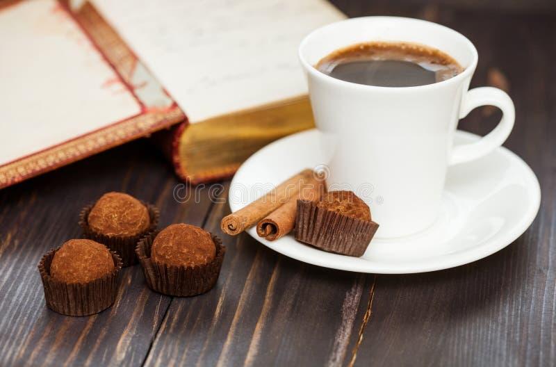 Schönes Stillleben: Schokoladentrüffeln, Zimt, ein Tasse Kaffee und ein geöffnetes Buch lizenzfreies stockfoto