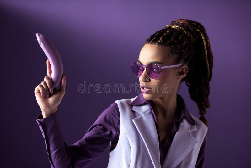 Schönes stilvolles Afroamerikanermädchen in der purpurroten Sonnenbrille, die Banane als Gewehr hält, lizenzfreies stockbild