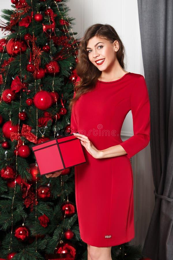 Schönes stilvolles Mädchen gekleidet in den roten Kleiderhaltungen mit rotem Kasten in ihren Händen nahe bei dem Baum des neuen J lizenzfreie stockbilder