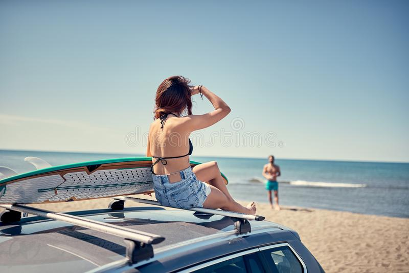 Schönes Surfermädchen, das auf dem Auto sitzt und zu s fertig wird stockfotografie