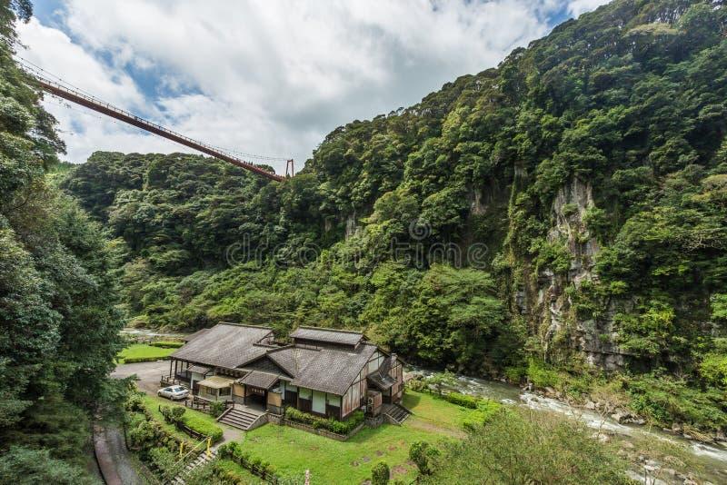 Schönes Tal und japanisches Haus in Wasserfall Kamikawa Otaki parken, Kagoshima lizenzfreies stockfoto