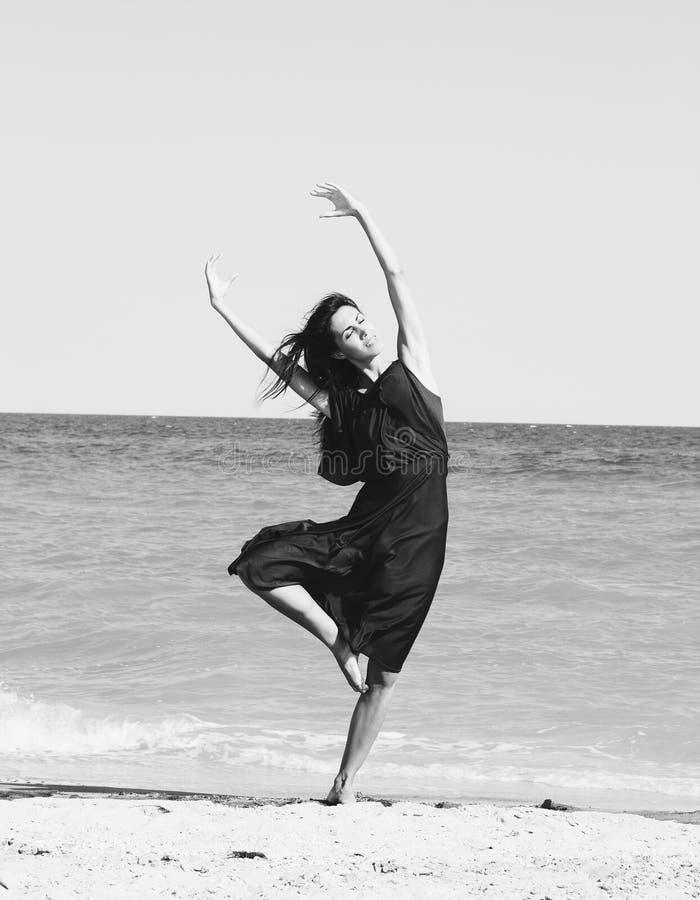Schönes Tanzen der jungen Frau auf dem Strand stockbild