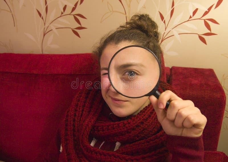 Schönes tennager Mädchen, das durch ein Vergrößerungsglas schaut lizenzfreies stockfoto