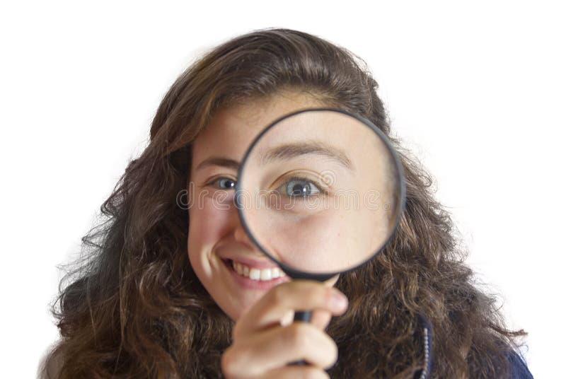 Schönes tennager Mädchen, das durch ein Vergrößerungsglas schaut stockfotografie