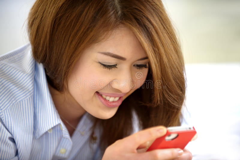 Schönes thailändisches jugendlich Lachen mit Handy stockbild