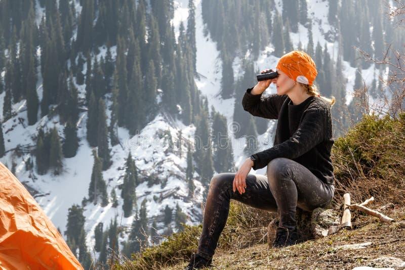 Schönes touristisches Mädchen sitzt nahe einem Zelt und betrachtet durch Ferngläser Schnee-mit einer Kappe bedeckten Bergen stockfotos