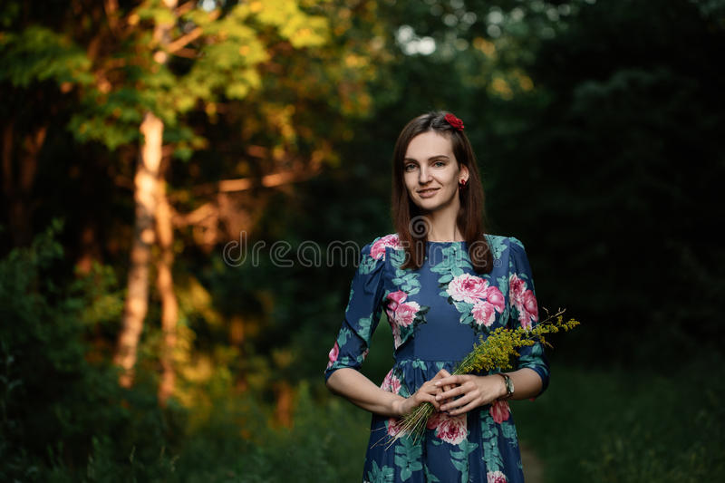 Schönes tragendes Kleid der jungen Frau des Brunette und Gehen auf das Waldaufflackern für Text und Design Lebensstil in der Stad stockbilder