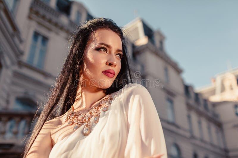 Schönes tragendes weißes Hochzeitskleid der jungen Frau auf altem Architekturhintergrund Zubehör und Schmuck stockbild