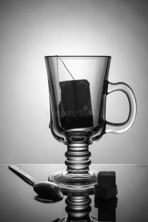 Schönes transparentes Glas mit Teebeutel Zucker und ein Löffel liegen auf dem Tisch Schönes Schwarzweiss-Bild lizenzfreies stockbild