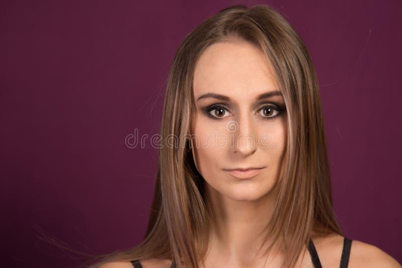 Schönes, trauriges Frauen-Porträt auf purpurrotem Hintergrund stockfotos