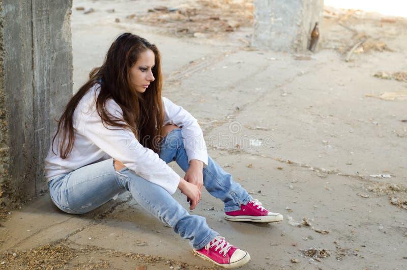 Schönes trauriges Mädchen, das auf dem Boden des verlassenen Gebäudes sitzt stockbild