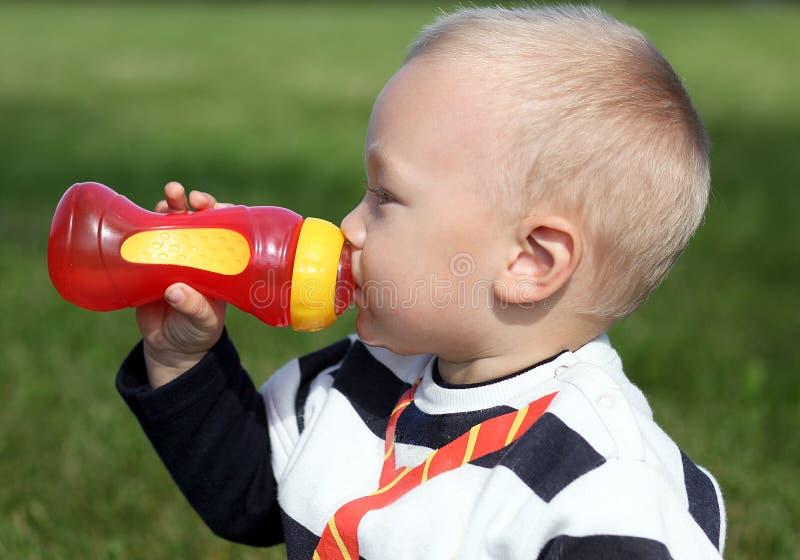 Schönes Trinken des kleinen Jungen lizenzfreie stockfotografie