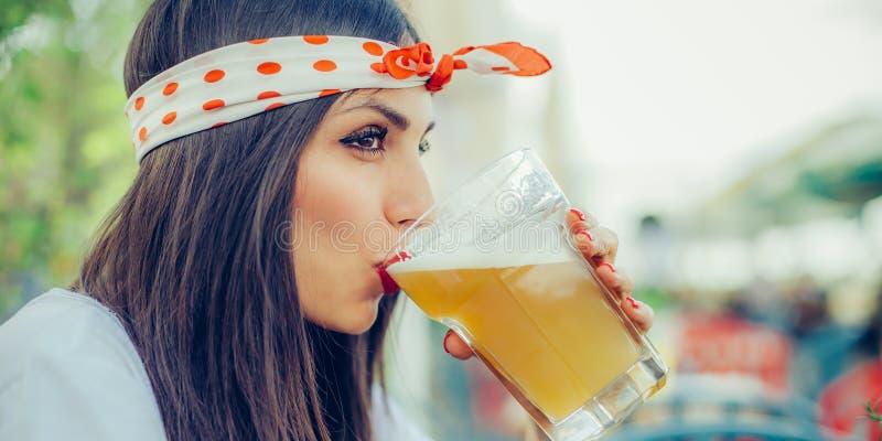 Schönes trinkendes Bier der jungen Frau und Genießen des Sommertages stockbild