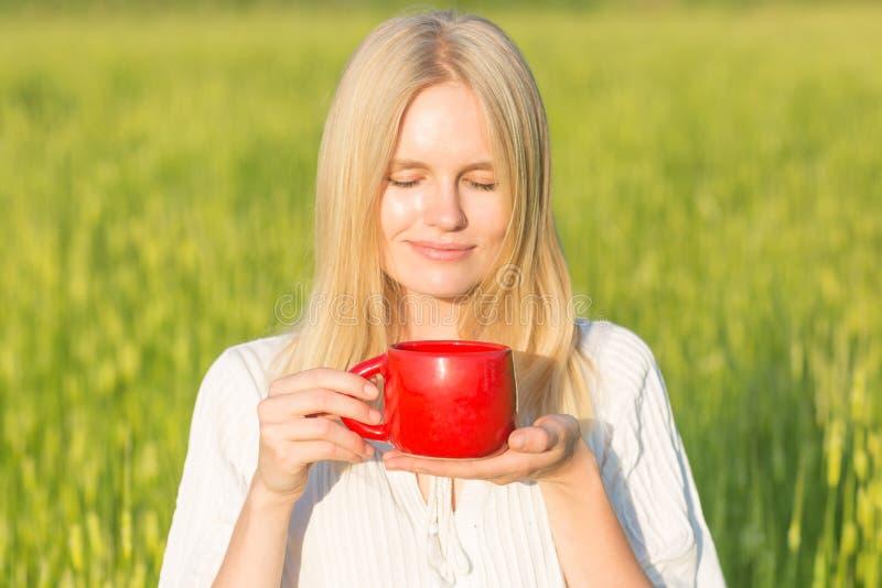 Schönes trinkendes Tee-/Kaffeefreien der jungen Frau Grüner Sommerfeldhintergrund stockfoto