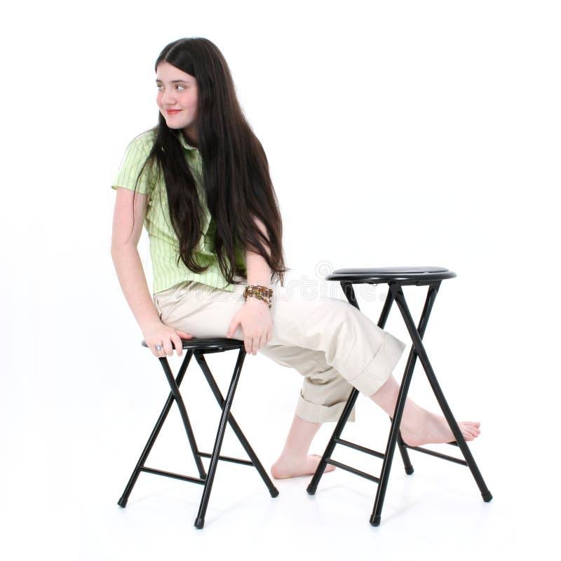 Schönes Tween-Mädchen, das auf Schemel sitzt lizenzfreie stockfotos