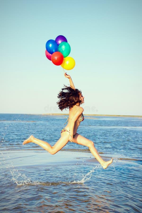 Schönes und athletisches Brunettemädchen mit bunten Ballonen springen stockfotos
