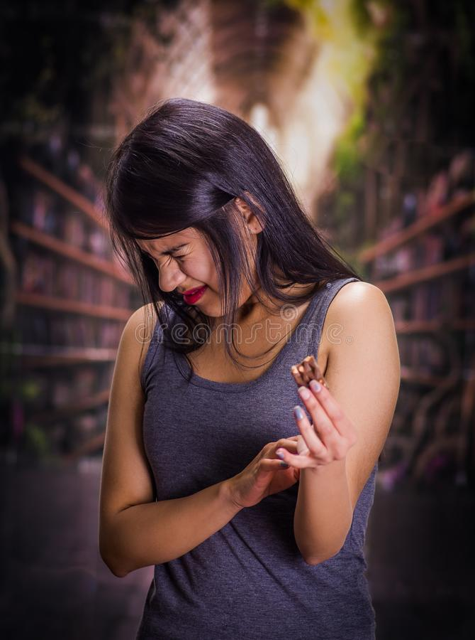 Schönes und einsames Mädchen, das unter anorexy leidet, in ihrer Hand ein Stück Schokolade hält und ein ekelhaftes Gesicht tut lizenzfreies stockbild
