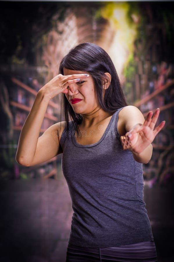 Schönes und einsames Mädchen, das unter anorexy leidet, in ihrer Hand ein Stück Schokolade hält und ihre Nase bedeckt, um zu tun lizenzfreie stockfotos