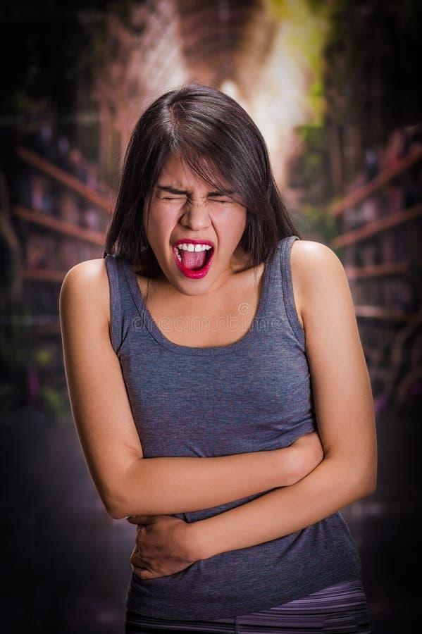 Schönes und einsames Mädchen, das unter den anorexy, leidenden Schmerz in seinem Magen in einem unscharfen Hintergrund leidet stockfotos